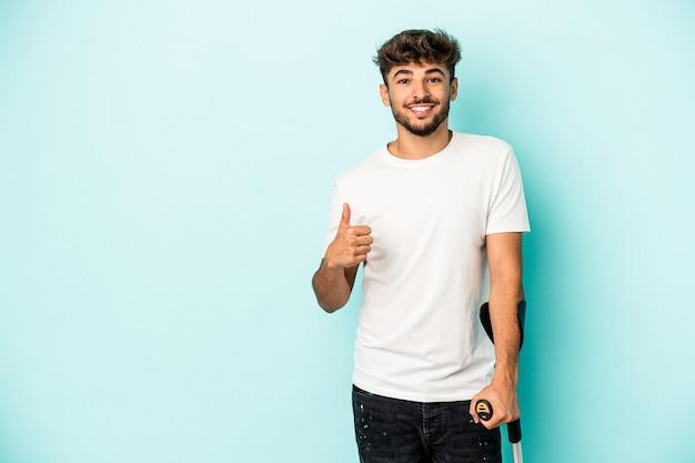 Jeune homme arabe avec des béquilles isolé sur fond bleu souriant et levant le pouce vers le haut