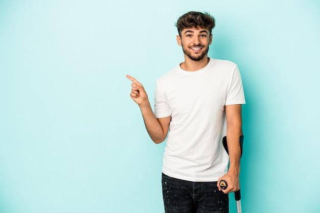 Jeune homme arabe avec des béquilles isolé sur fond bleu souriant et pointant de côté, montrant quelque chose dans un espace vide.