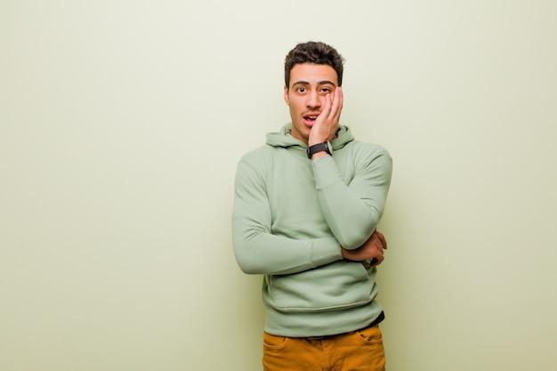 Jeune homme arabe bouche bée en état de choc et d'incrédulité, avec la main sur la joue et le bras croisés, se sentant stupéfait et étonné contre un mur plat