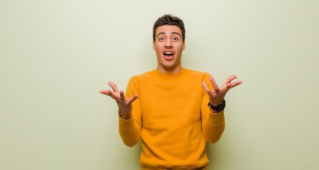 Jeune homme arabe bouche bée et étonné, choqué et étonné d'une incroyable surprise contre un mur plat