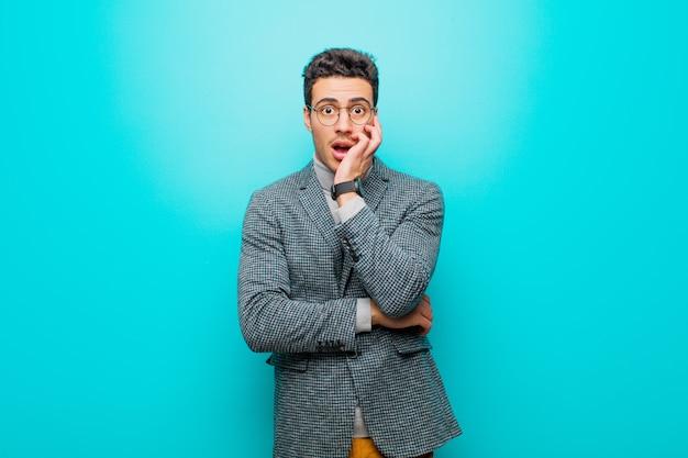 Jeune homme arabe bouche bée sous le choc et l'incrédulité, la main sur la joue et le bras croisés, se sentant stupéfait et étonné contre le mur bleu