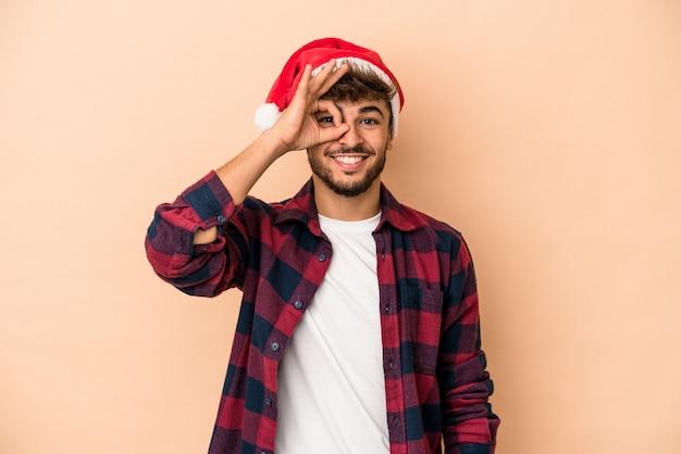 Jeune homme arabe célébrant noël isolé sur fond beige excité en gardant un geste ok sur les yeux.