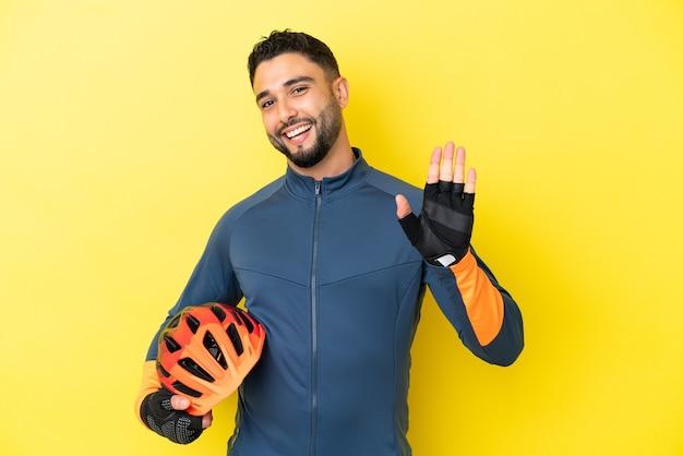 Jeune homme arabe cycliste isolé sur fond jaune saluant avec la main avec une expression heureuse