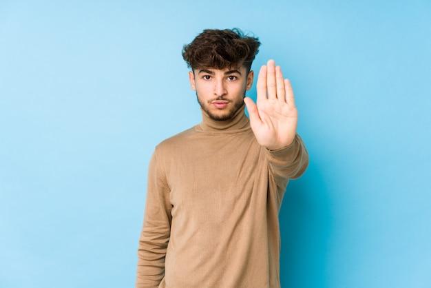 Jeune homme arabe debout avec la main tendue montrant le panneau d'arrêt