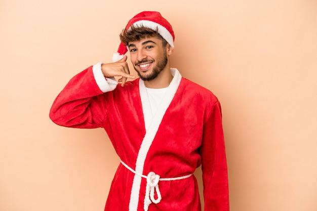 Jeune homme arabe déguisé en père noël isolé sur fond beige montrant un geste d'appel de téléphone portable avec les doigts.