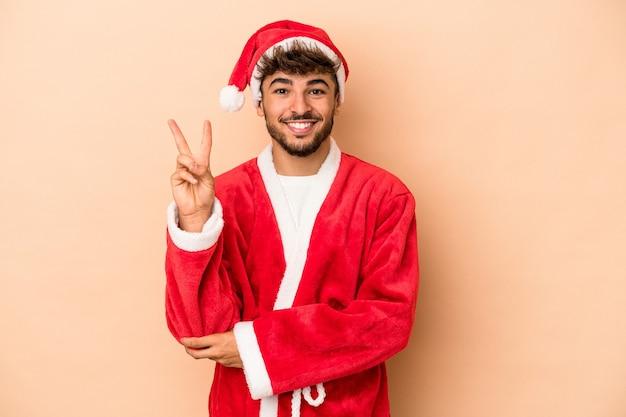 Jeune homme arabe déguisé en père noël isolé sur fond beige montrant le numéro deux avec les doigts.