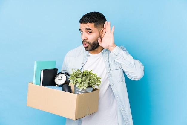 Jeune homme arabe déménageant dans une nouvelle maison isolée en essayant d'écouter un commérage.