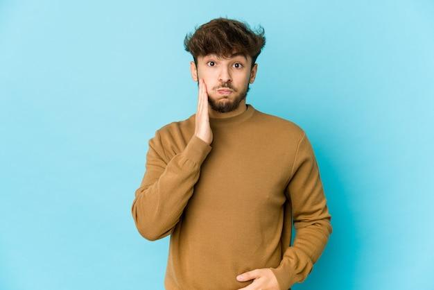 Jeune homme arabe sur un espace bleu souffle sur les joues, a une expression fatiguée. concept d'expression faciale.