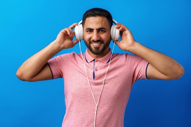 Jeune homme arabe heureux avec des écouteurs écoutant de la musique sur fond bleu