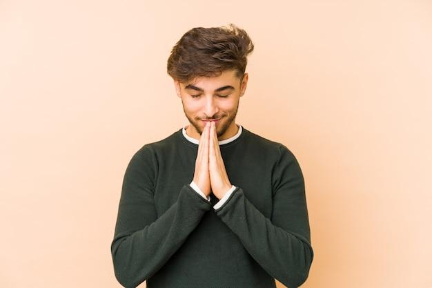 Jeune homme arabe isolé sur beige tenant par la main en priant près de la bouche, se sent confiant.