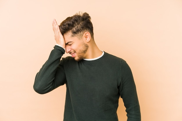 Jeune homme arabe isolé sur un espace beige oubliant quelque chose, giflant le front avec la paume et fermant les yeux.