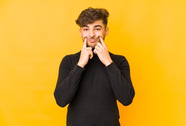 Jeune homme arabe isolé sur un espace jaune doutant entre deux options.