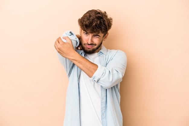Jeune homme arabe isolé sur fond beige ayant une douleur au cou due au stress, en le massant et en le touchant avec la main.