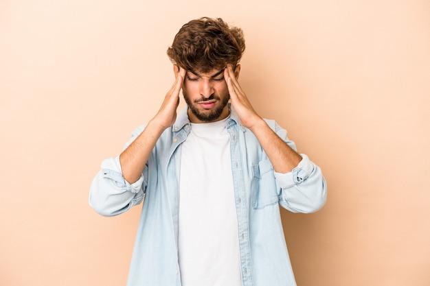 Jeune homme arabe isolé sur fond beige ayant mal à la tête, touchant le devant du visage.