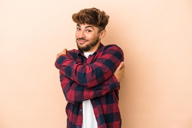 Jeune homme arabe isolé sur fond beige câlins, souriant insouciant et heureux.