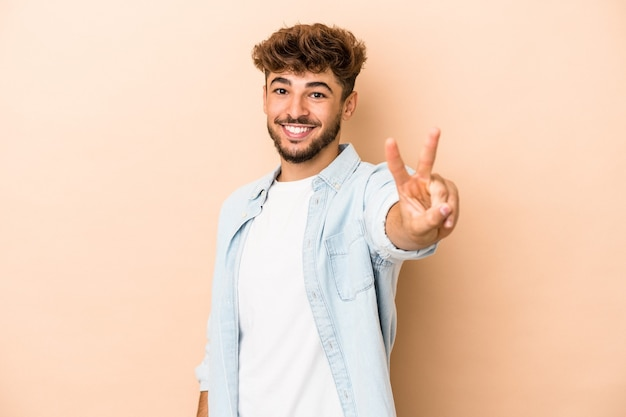 Jeune homme arabe isolé sur fond beige joyeux et insouciant montrant un symbole de paix avec les doigts.