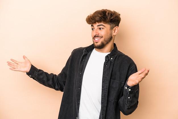 Jeune homme arabe isolé sur fond beige joyeux riant beaucoup. notion de bonheur.