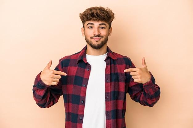 Jeune homme arabe isolé sur fond beige personne pointant à la main vers un espace de copie de chemise, fier et confiant