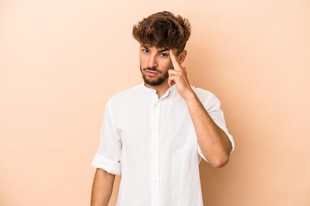Jeune homme arabe isolé sur fond beige pointant le temple avec le doigt, pensant, concentré sur une tâche.