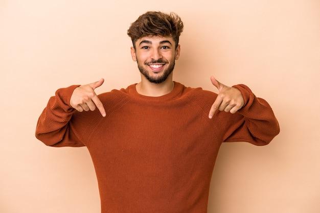 Jeune homme arabe isolé sur fond beige pointe vers le bas avec les doigts, sentiment positif.