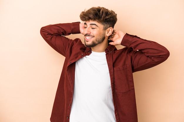 Jeune homme arabe isolé sur fond beige se sentant confiant, les mains derrière la tête.