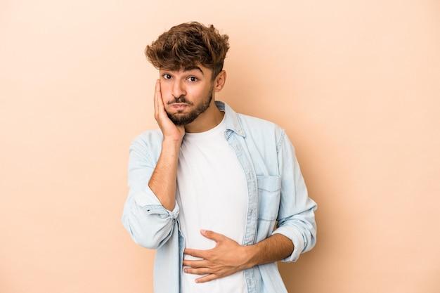 Jeune homme arabe isolé sur fond beige souffle les joues, a une expression fatiguée. concept d'expression faciale.