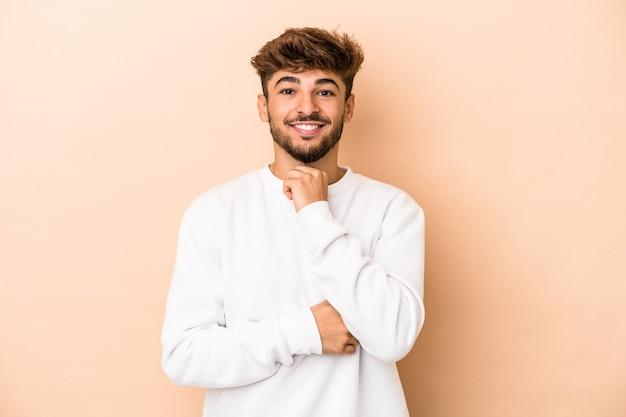Jeune homme arabe isolé sur fond beige souriant heureux et confiant, touchant le menton avec la main.