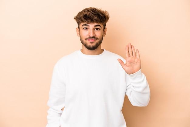 Jeune homme arabe isolé sur fond beige souriant joyeux montrant le numéro cinq avec les doigts.