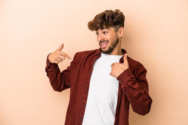 Jeune homme arabe isolé sur fond beige surpris pointant du doigt, souriant largement.
