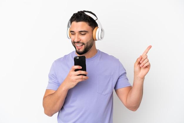 Jeune homme arabe isolé sur fond blanc, écouter de la musique avec un mobile et chanter