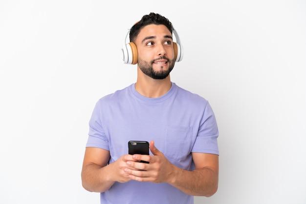 Jeune homme arabe isolé sur fond blanc, écouter de la musique avec un mobile et penser