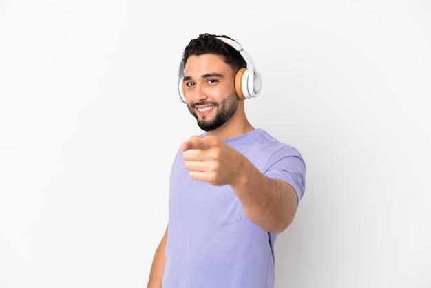 Jeune homme arabe isolé sur fond blanc, écouter de la musique et pointant vers l'avant