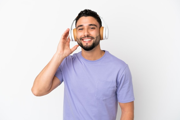 Jeune homme arabe isolé sur fond blanc, écouter de la musique