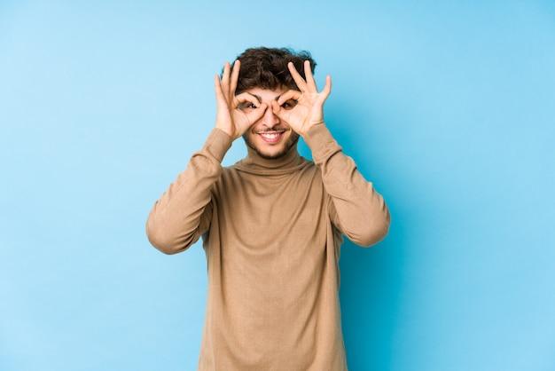Jeune homme arabe isolé montrant bien signe sur les yeux
