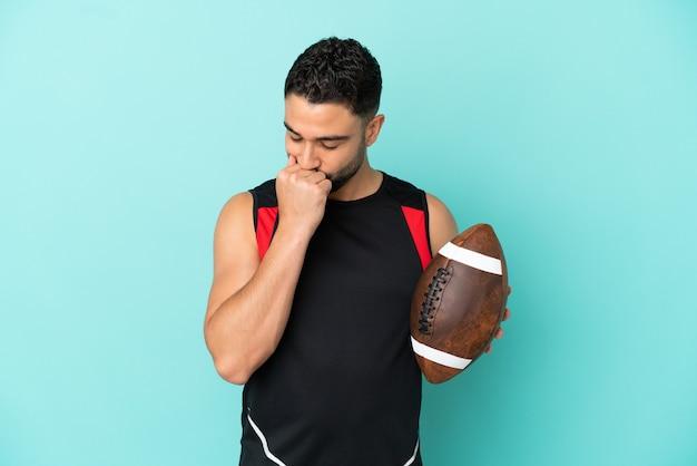 Jeune homme arabe jouant au rugby isolé sur fond bleu ayant des doutes