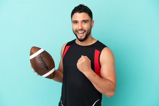 Jeune homme arabe jouant au rugby isolé sur fond bleu célébrant une victoire