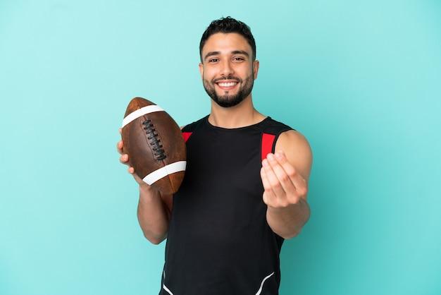 Jeune homme arabe jouant au rugby isolé sur fond bleu faisant un geste d'argent