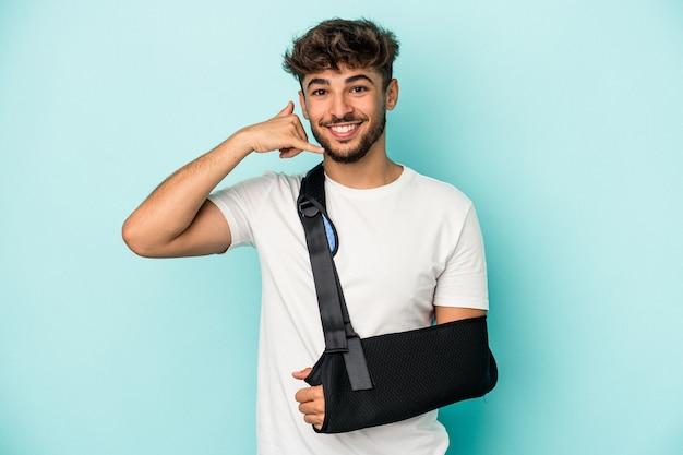 Jeune homme arabe avec main cassée isolé sur fond bleu montrant un geste d'appel de téléphone portable avec les doigts.