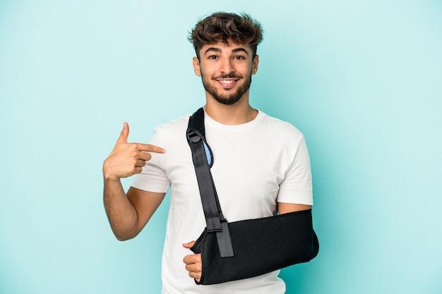 Jeune homme arabe avec main cassée isolé sur fond bleu personne pointant à la main vers un espace de copie de chemise, fier et confiant
