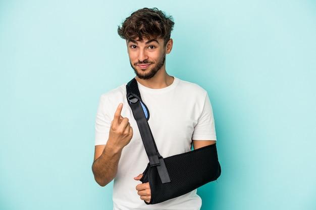 Jeune homme arabe avec main cassée isolé sur fond bleu pointant avec le doigt vers vous comme s'il vous invitait à vous rapprocher.