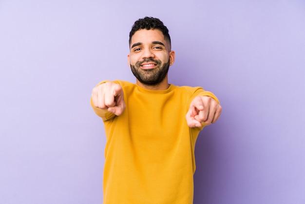 Jeune homme arabe métisse isolé sourires joyeux pointant vers l'avant.