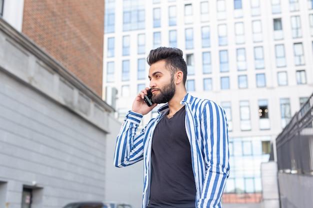 Jeune homme arabe moderne avec téléphone portable dans la rue. portrait en plein air.