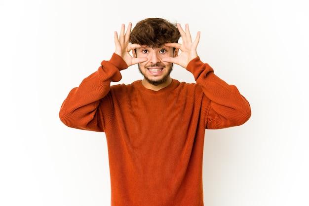 Jeune homme arabe sur un mur blanc en gardant les yeux ouverts pour trouver une opportunité de succès