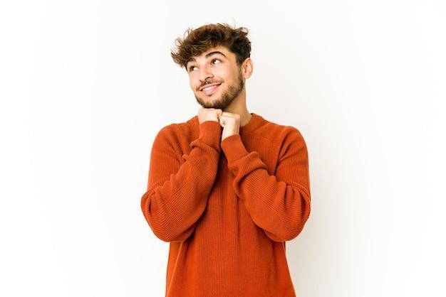 Jeune homme arabe sur un mur blanc garde les mains sous le menton, regarde joyeusement de côté.