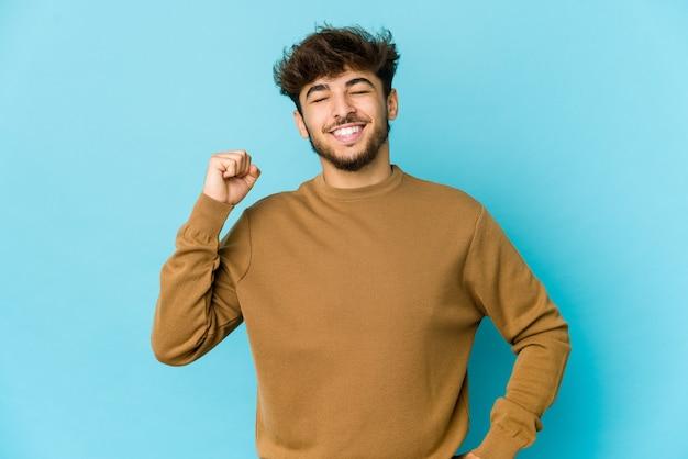 Jeune homme arabe sur mur bleu célébrant une victoire, passion et enthousiasme, expression heureuse.