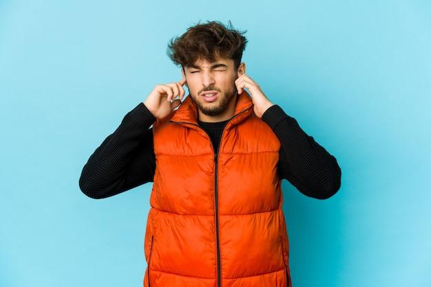 Jeune homme arabe sur un mur bleu couvrant les oreilles avec les doigts, stressé et désespéré par un bruit ambiant.