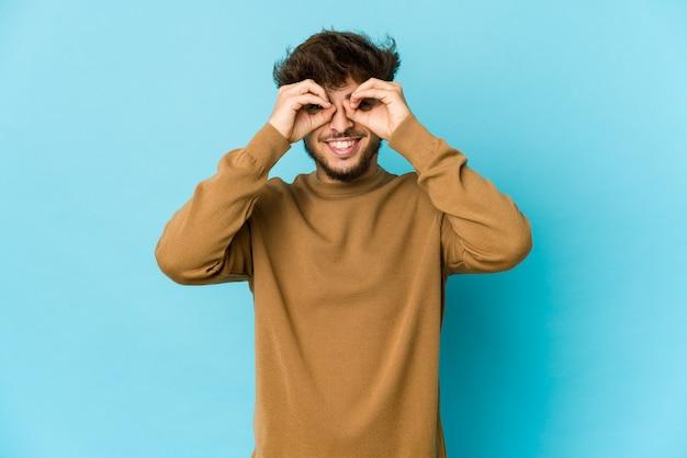 Jeune homme arabe sur un mur bleu montrant un signe correct sur les yeux