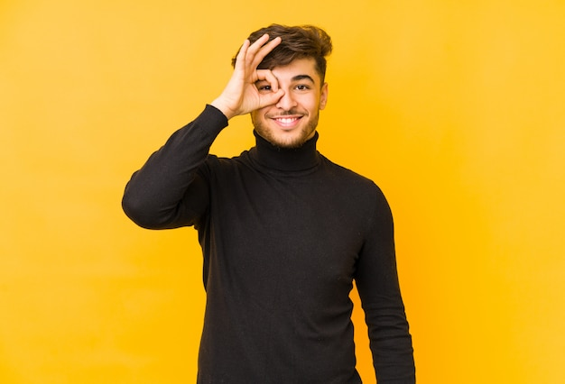 Jeune homme arabe sur un mur jaune excité en gardant le geste ok sur les yeux.