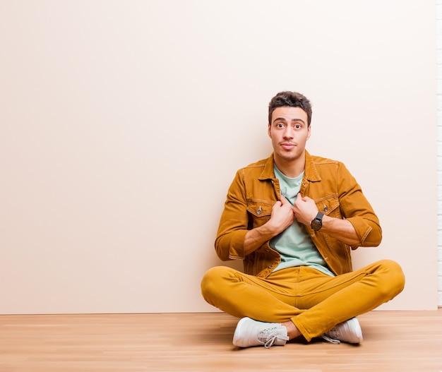 Jeune homme arabe pointant vers soi avec un air confus et perplexe, choqué et surpris d'être choisi assis sur le sol