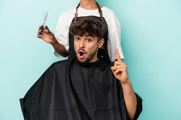 Jeune homme arabe prêt à se faire couper les cheveux isolé sur fond bleu ayant une idée, concept d'inspiration.